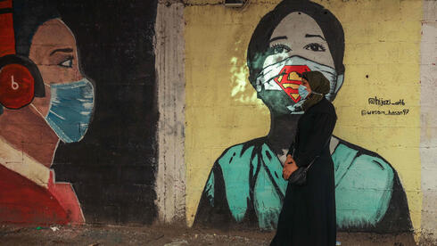 A Palestinian women walks past a coronavirus-inspired mural along a street in Gaza