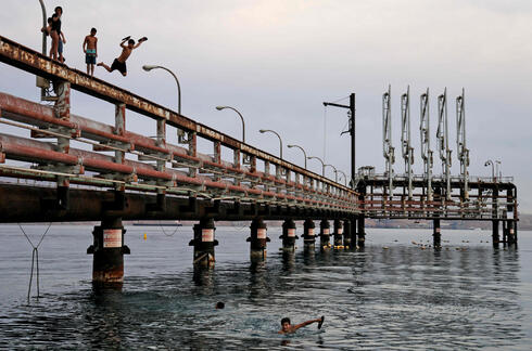 Youths jump into the Red Sea water off an abandoned oil jetty in Eilat, Feb. 2021