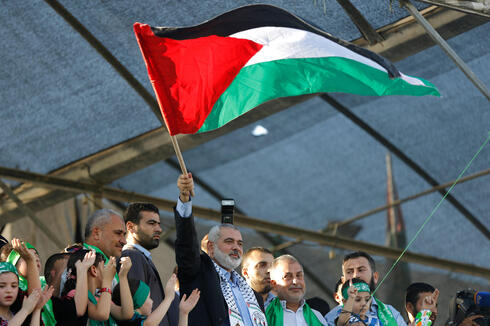 Hamas' top leader in the Gaza Strip Ismail Haniya (C) waves the Palestinian flag during a rally in Gaza C