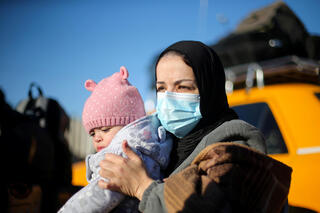 A Palestinian woman carrying her child waits to leave Gaza through the Rafah border crossing