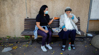 A woman holds a slice of pizza, which was handed to her after she was vaccinated against the coronavirus disease (COVID-19) as part of an initiative to encourage people to get vaccinated, near a temporary vaccination centre in Tel Aviv