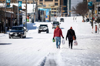 Texans carry supplies through the streets of Austin during the recent winter storm