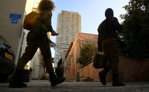 soldiers walk past a house in Tel Aviv