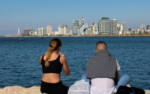 A young couple share a picnic in front of the skyline of Tel Aviv