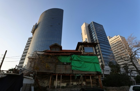 An old wooden house stands in front of modern buildings in the Israeli coastal city