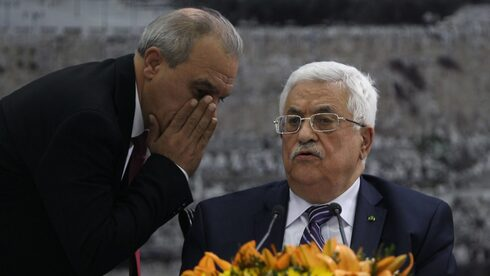 Director of Palestinian General Intelligence in the West Bank Majid Faraj whispers to Palestinian President Mahmoud Abbas during a meeting in Ramallah, April 2014