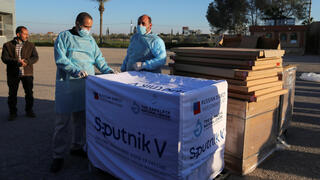 Palestinian health workers stand next to a shipment of Russia's Sputnik V vaccine sent by United Arab Emirates, amid the coronavirus disease (COVID-19) outbreak, at Rafah crossing in the southern Gaza Strip