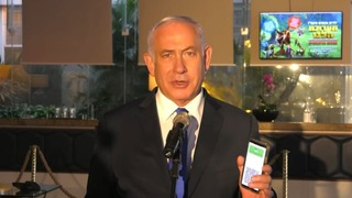 Netanyahu holds up his Green Pass, given to people who'd received two vaccine shots