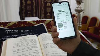 Digital Green Pass being shown on the phone in synagogue