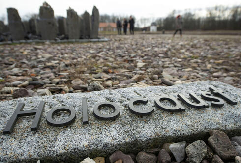 people walk behind the writing 'Holocaust' during the international Holocaust remembrance day in the former the Nazi concentration camp Buchenwald