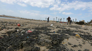 Tar is seen on the beach in the aftermath of an oil spill that drenched much of the Mediterranean, in Tyre nature reserve, Lebanon