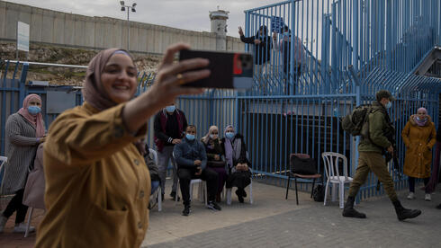Palestinians take a selfie after receiving the coronavirus vaccine from an Israeli medical team at the Qalandia checkpoint between the West Bank and Jerusalem, Feb. 23, 2021