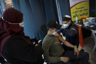 An Israeli medic administers the coronavirus vaccine to a Palestinian at the Qalandia checkpoint between the West Bank and Jerusalem, Feb. 23, 2021