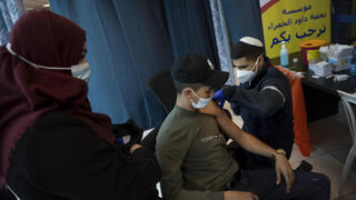 Israeli medics administer the Pfizer coronavirus vaccine to Palestinians at the Qalandia checkpoint between the West Bank and Jerusalem, Feb. 23, 2021