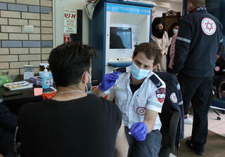 An Israeli healthcare worker vaccinating a Palestinian against coronavirus at the Qalandia Checkpoint
