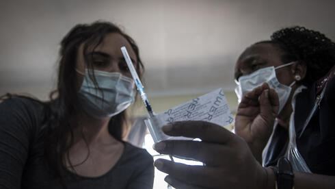 A health care worker is shown a Johnson & Johnson Covid-19 vaccine at the government hospital in Klerksdorp, South Africa,