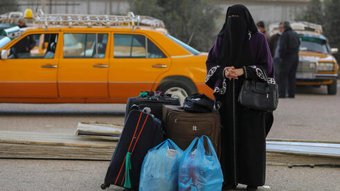 A Palestinian woman waits to leave Gaza through Rafah border crossing with Egypt,