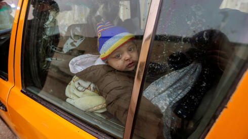 A Palestinian boy looks out of a car window as he waits to leave Gaza with his family through Rafah border crossing