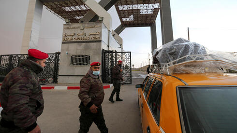 embers of Palestinian security forces keep watch as a taxi carrying passengers arrives at the gate of Rafah border crossing with Egypt, in the southern Gaza Strip