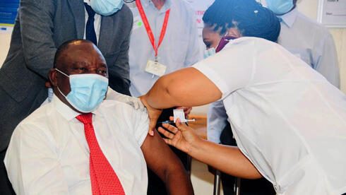 s South African President Cyril Ramaphosa (L) being vaccinated with the Johnson & Johnson Covid-19 coronavirus vaccine
