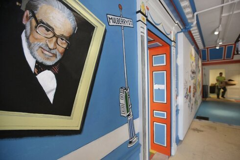 a mural that features Theodor Seuss Geisel, left, also known by his pen name Dr. Seuss, covers part of a wall near an entrance at The Amazing World of Dr. Seuss Museum, in Springfield, Mass.