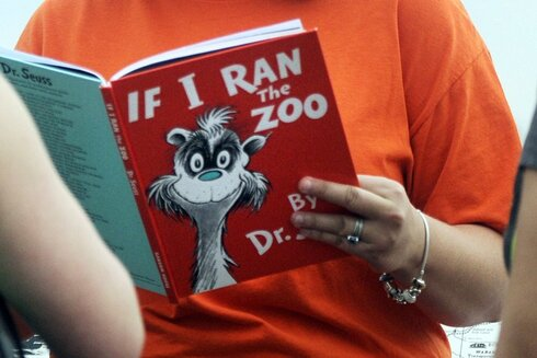 "Courtney Keating, education coordinator of The Literacy Center in Evansville, Ind., reads ""If I Ran the Zoo,"" By Dr. Seuss, to passersby during an event to promote literacy along the Evansville Riverfront."