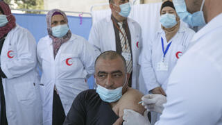 A Palestinian medic receives the Moderna COVID-19 vaccine in the West Bank city of Bethlehem