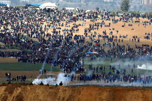 Israeli soldiers shoot tear gas from the Israeli side of the Israel-Gaza border as Palestinians protest on the Gaza side of the border, March 30, 2018