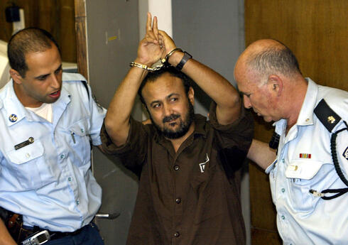 Marwan Barghouti, a popular Palestinian leader, gestures as Israeli police bring him into the District Court for his judgment hearing in Tel Aviv May 20, 2004/