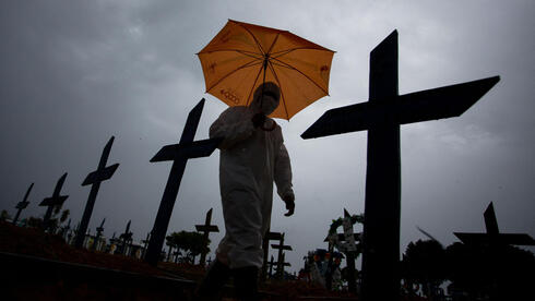 a worker wearing a protective suit and carrying an umbrella walks past the graves of COVID-19 victims at the Nossa Senhora Aparecida cemetery, in Manaus