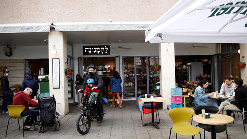 Guests sit and take away food and drinks from a Tel Aviv cafe as Israel further the eases coronavirus restrictions, March 7, 2021