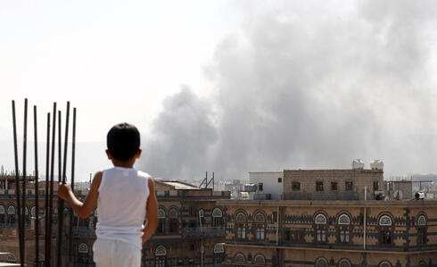 A child looks on as fighting rages on the outskirts of Sanaa, Yemen
