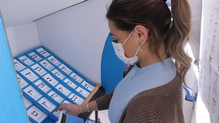 A woman donning a face mask demonstrates voting during COVID-19 pandemic