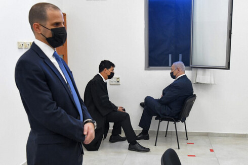 Prime Minister Benjamin Netanyahu (R) talks to his lawyer ahead of a hearing in his corruption trial at the Jerusalem district court, on February 8, 2021