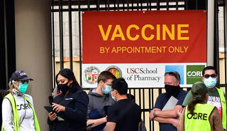 People wearing face masks are seen in front of a COVID-19 vaccination facility in Los Angeles, CA