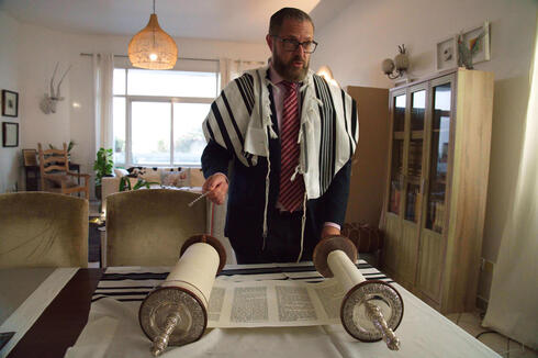 Alex Peterfreund, a co-founder of Dubai's Jewish community and its cantor, prepares to read from the Torah in Dubai
