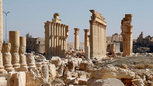 picture shows the damaged Arch of Triumph and surrounding columns in Syria's Roman-era ancient city of Palmyra