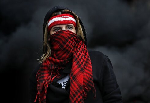 a protester covers her face with a scarf, as protesters block a main highway in the town of Zouk Mosbeh, north of Beirut, Lebanon