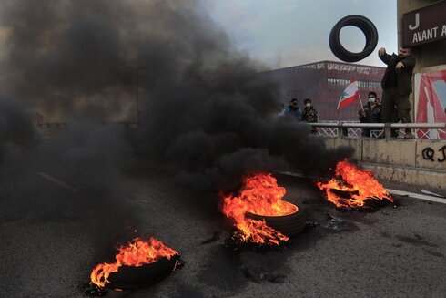 a protester throws a tire into burning tires to block a main highway, in the town of Jal el-Dib, north of Beirut, Lebanon