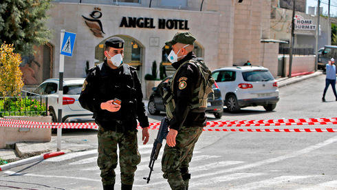 Palestinian police stand outside the Angel Hotel in Beit Jala at the start of the pandemic