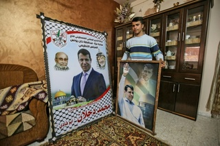 A member of Mohammed Dahlan's family displays pictures of the exiled Palestinian politician at their home in Khan Yunis, Gaza