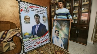 A member of Mohammed Dahlan's family displays pictures of the exiled Palestinian politician at their home in the Khan Yunis