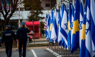 Police officers walk past Kosovan and Israeli flags displayed during a ceremony in Pristina in February after the countries established diplomatic ties