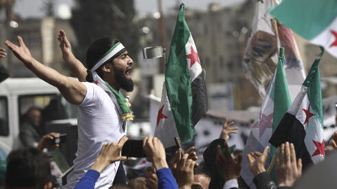 n anti-Syrian government protester shouts slogans as others wave revolutionary flags, to mark 10 years since the start of a popular uprising