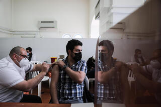 A man being vaccinated against coronavirus at a clinic in Jerusalem