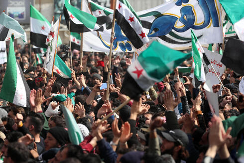 Protesters wave flags of the Syrian opposition during a demonstration in Syria's rebel-held city of Idlib