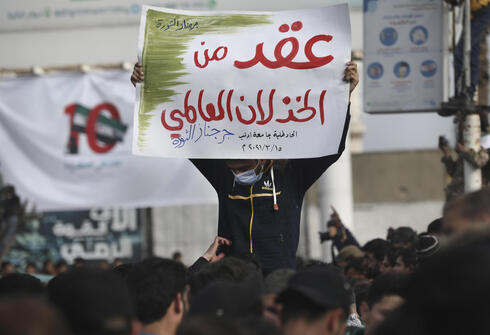 """An anti-government protester holds up an Arabic placard that reads in part: """"A decade of a global letdown"""