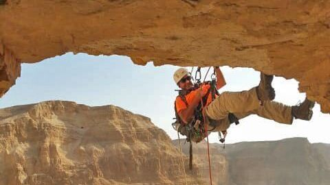 An archeologist rappels down the cliff into the Horor cave in the Judean Desert where rare discoveries were made