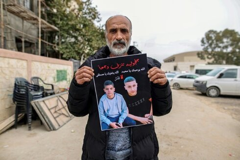 The father of Mohammed Adas holds a poster bearing his picture a day after his funeral in the Arab Israeli town of Jaljulia last week