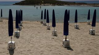 Rows of closed parasols on a nearly empty stretch of Nissi beach with a few beachgoers in the distance in Cyprus' seaside resort of Ayia Napa, a favorite among tourists from Europe and beyond